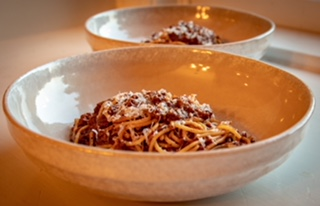 Beef bolognese over pasta in bowls with parmesan cheese on top