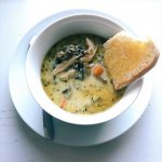chicken and mushroom wild rice soup with a piece of crusty bread, in a white bowl