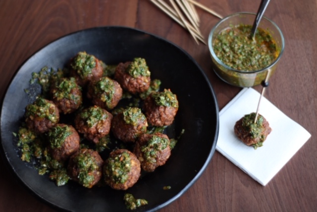 Meatballs on a plate with chimichurri sauce on top and on the side