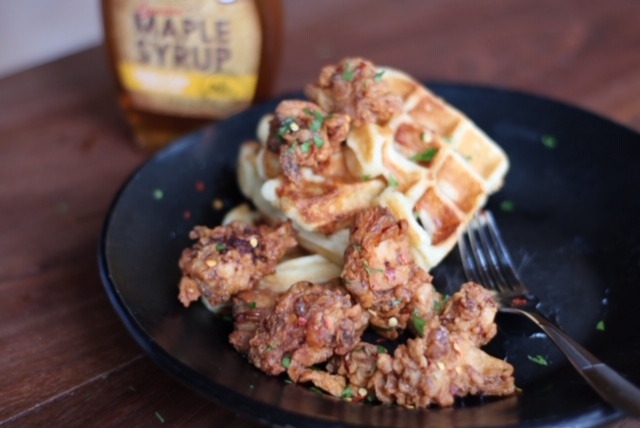 fried chicken and waffles with maple syrup, parsley, and crushed red pepper on top
