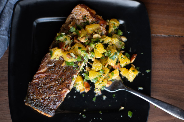 crispy skinned salmon, cooked, with smoked almond and orange salsa on a black plate