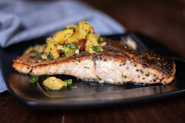 crispy-skinned salmon, cooked, with smoked almond and orange salsa on top on a black plate