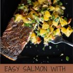 crispy-skinned salmon topped with smoked almond and orange salsa on a black plate