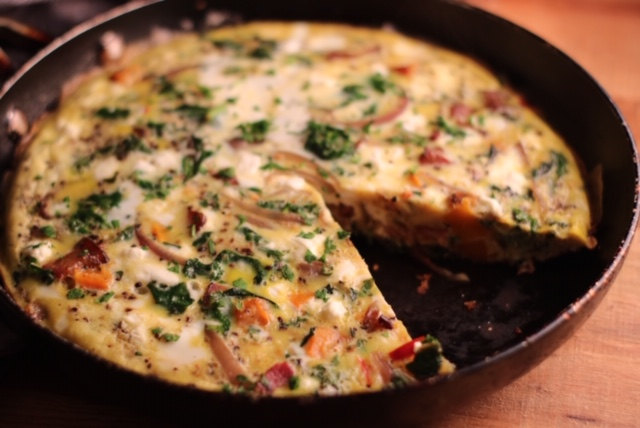 Kale, butternut squash, and pancetta frittata in a skillet with a slice taken out.