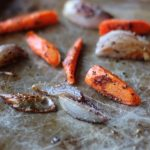 roasted carrots and shallots on a baking sheet