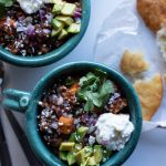 sweet potato black bean chili with greek yogurt, chopped onions, avocado, cilantro, and feta on top in 2 bowls with fry bread on the side