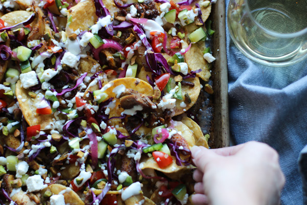 colorful chicken shawarma nachos on a sheet pan with a glass of wine and a hand grabbing a chip