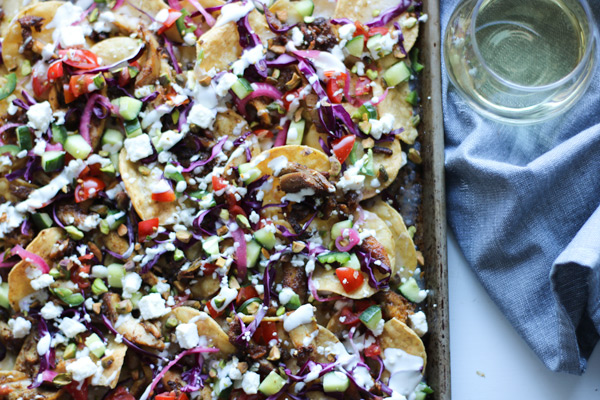 colorful chicken shawarma nachos on a sheet pan with a glass of wine