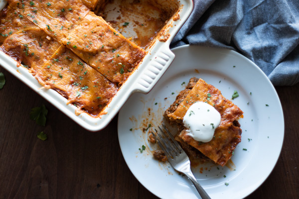 beef enchiladas in a pan with one square cut out, served on a plate with sour cream on top