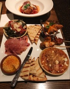Mediterranena Tapas Plate from Green Valley Grill Restaurant - hummus, speck, pita, samosas, and charred broccoli on a square plate