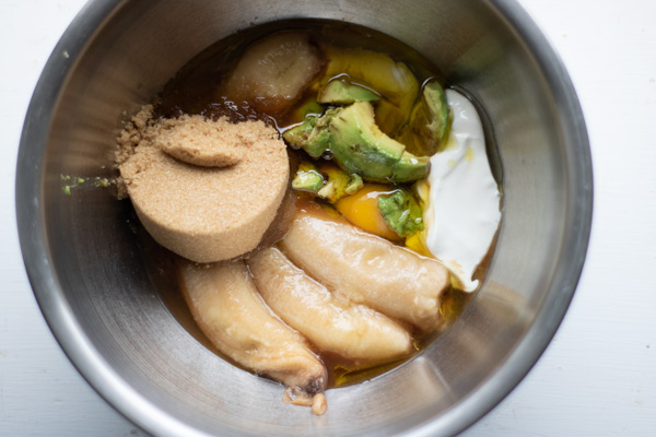 brown sugar, ripe bananas, avocado, egg, and sour cream in a bowl before mixing for muffins