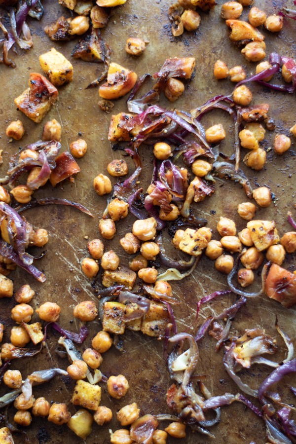 Chickpeas, red onions, and apples, tossed in a curry spice blend on a baking sheet