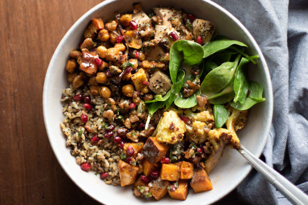 roasted veggie bowl with squash, cauliflower, chickpeas, apples, spinach, and pomegranate seeds