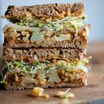 roasted cauliflower sandwich with melted provolone, sprouts, crispy onions and sriracha mayo on whole wheat toast