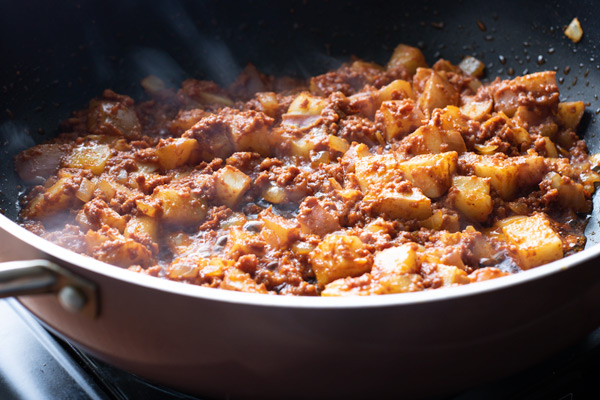 Chorizo and potato filling being cooked in a skillet for Chorizo Potato Breakfast Tacos
