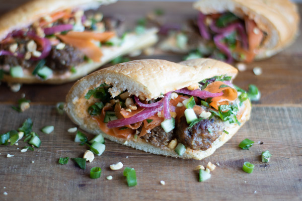 a meatball banh mi sandwich with pickled carrots and onions, fresh herbs, jalapeno, cucumber, and chopped peanuts on a board