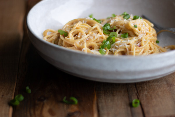 roasted garlic miso butter noodles swirled in a bowl, garnished with Parmesan and green onions