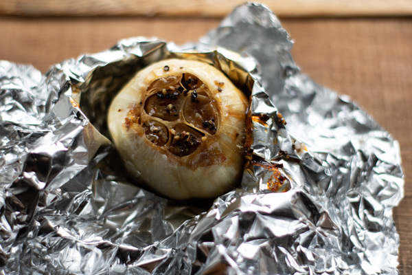 a head of roasted garlic in aluminum foil