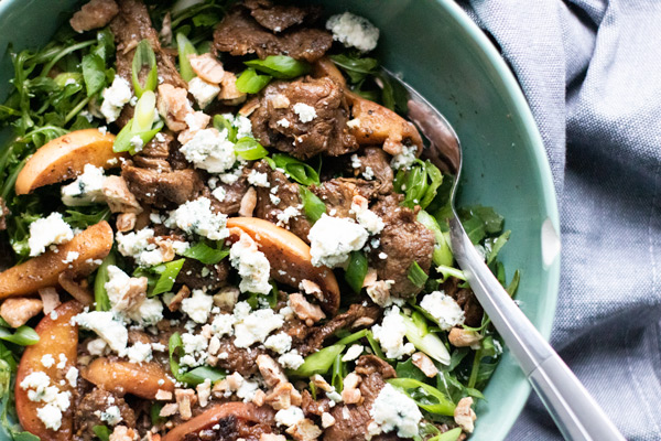 steak and apple salad with arugula, blue cheese, and chopped pralines in a green bowl with a fork