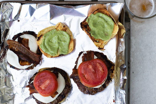3 burgers on a sheet pan with the top buns off to the side, spread with spicy basil sauce