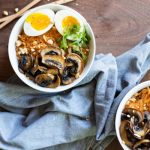 coconut curry ramen noodles in a white bowl, topped with mushrooms, a split soft boiled egg, green onions, and chopped peanuts with a blue towel and chopsticks