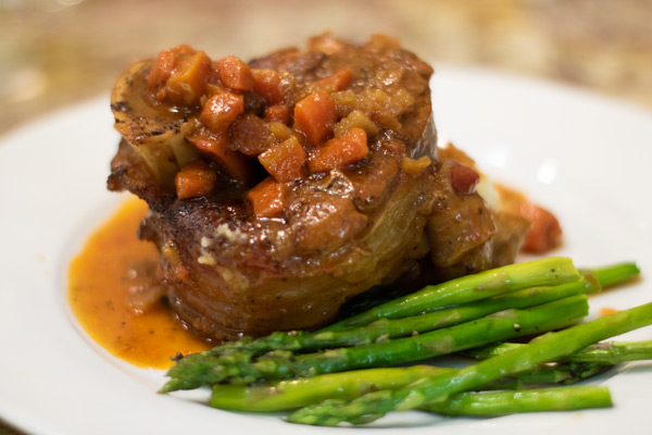 osso bucco with carrots and onions on top and asparagus on the side