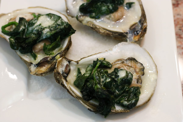 three oysters on a pile of salt on a plate with spinach cream sauce on top