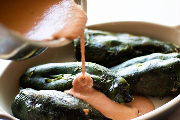 stuffed poblano peppers in a dish with tomato cream sauce being poured over top
