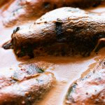 stuffed poblano peppers in tomato cream sauce baked in a dish