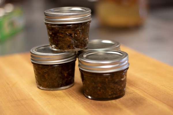 4 small mason jars of bacon jam on a wooden cutting board