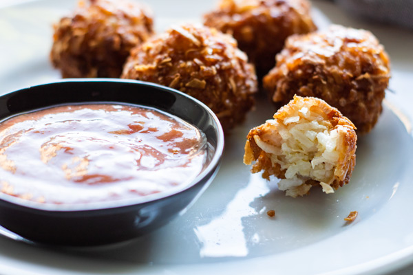 coconut fried rice balls on a white plate with a small dish of spicy peach dipping sauce