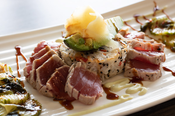 tuna sushi fanned around a jasmine rice cake on a plate, topped with ginger and two sauces