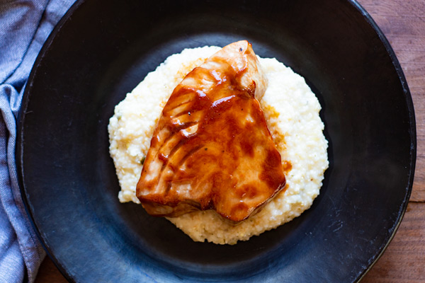 BBQ Tuna over Jalapeno Cheddar Grits on a black plate