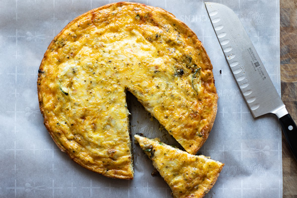 farmer's market vegetable frittata on a cutting board with a slice cut out