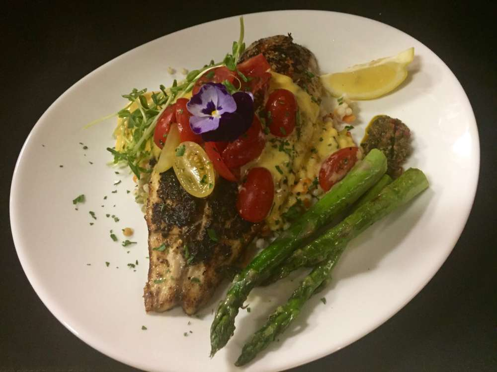 the Voodoo snapper entree at Russo's Bistro & Bar: snapper over couscous with tomatoes over top and a smoked tomato hollandaise, asparagus on the side