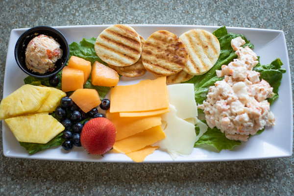 a platter of fresh fruit, cheeses, toasted pita, and scratch made shrimp salad