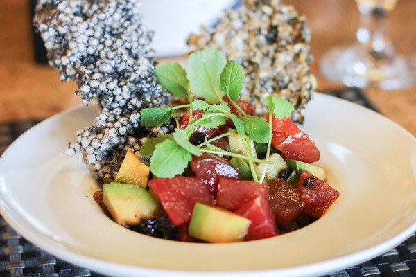 tuna poke in a bowl garnished with tapioca squid ink crackers