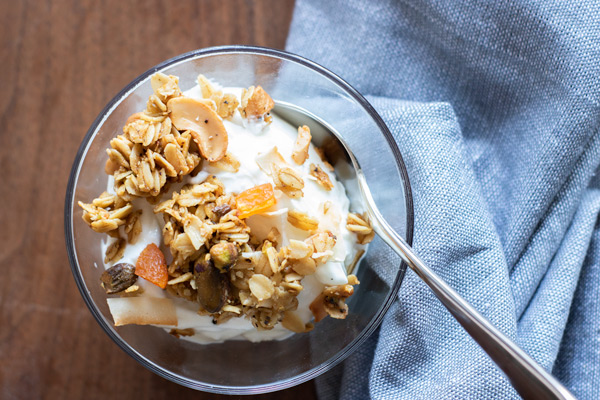 chaat masala granola on greek yogurt, in a small bowl with a spoon