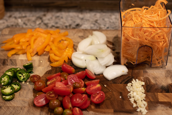 sliced cherry tomatoes, peppers, onions, garlic, and spiralized sweet potatoes on a cutting baord