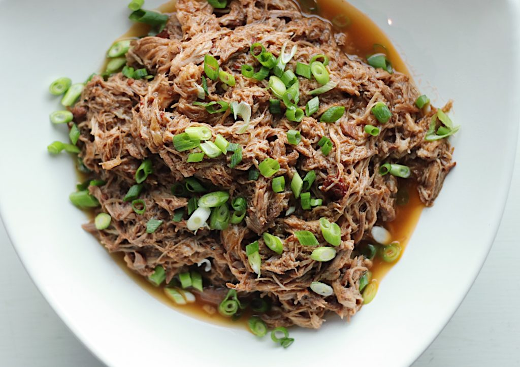 Apple Cider Pulled Pork, garnished with green onions, in a white bowl