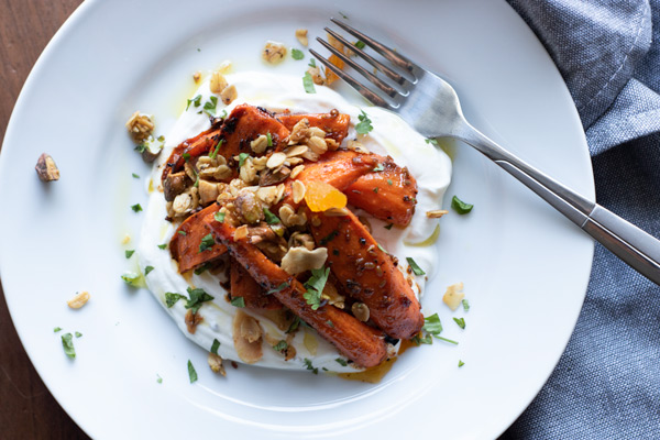 roasted carrots on a swirl of yogurt, topped with granola and chopped cilantro on a white plate with a fork