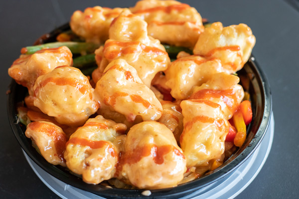 battered and fried cauliflower with peppers and rice in a bowl