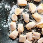 Pumpkin Gnocchi tossed in flour on a black plate