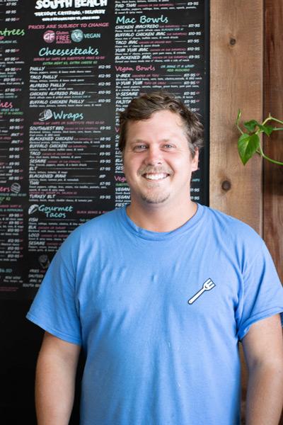 Wayne Everhart Jr. standing in front of South Beach's menu board