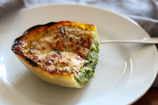 Half of a spaghetti squash filled with kale and topped with a cheesy crust on a white plate