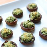 Stuffed mushrooms with kale and ream cheese on a white plate