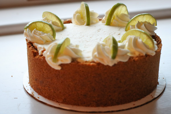 A key lime pie with graham cracker crust, decorated with lime wedges
