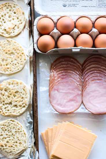 Toasted English muffins on a sheet pan, eggs in a carton, Canadian bacon, and slices of American cheese laid out to make breakfast sandwiches