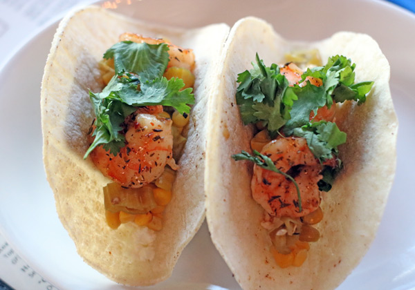 two shrimp tacos topped with cilantro on a white plate