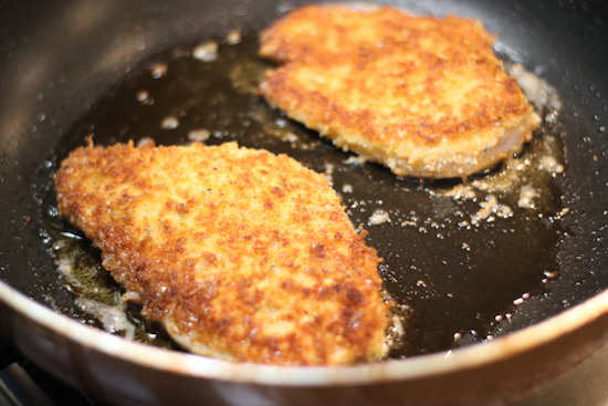 2 pieces of Crisp Pecorino Romano Chicken cooking in a skillet